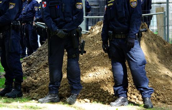 Riot Police-Einheiten bewachen bei der Räumung der besetzten Votivkirche einen Erdhügel
