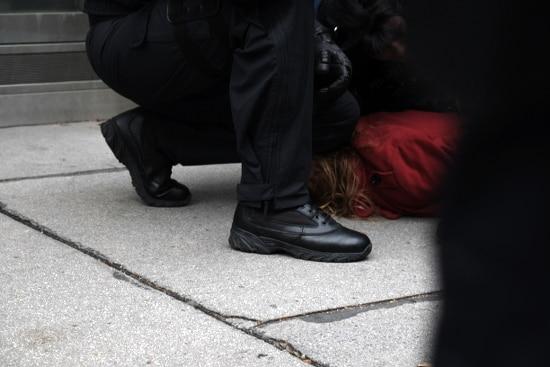 """Eine zu Boden geworfene friedliche Antifaschistin, wird von drei Polizist_innen """"fixiert"""""""