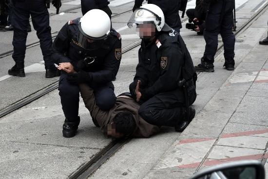 Antifaschistischer Demonstrant auf die Straßenmitte geschleppt und mit Handschellen gefesselt.