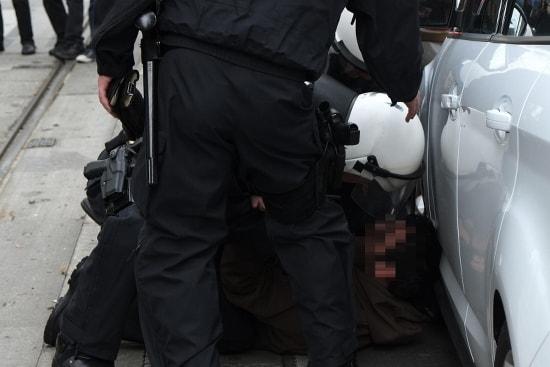 Antifaschist wird nach Befehl zu Boden gerungen und gegen ein haltendes Fahrzeug gedrückt.