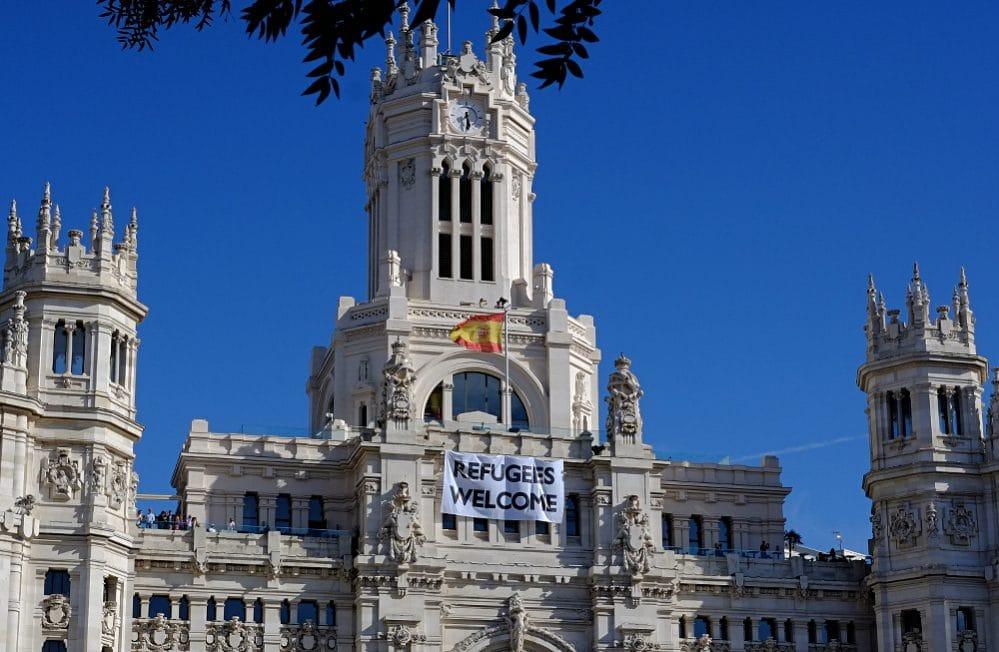 Refugees Welcome: 8x4 Meter großes Transparent der Stadtverwaltung Madrid am Palacio de Cibeles. Die Hauptstadt Madrid ist neben Barcelona und Valencia die dritte große Stadt Spaniens, die sich dem Netzwerk der Städte als Zufluchtsorte (red de ciudades refugio) anschloss.