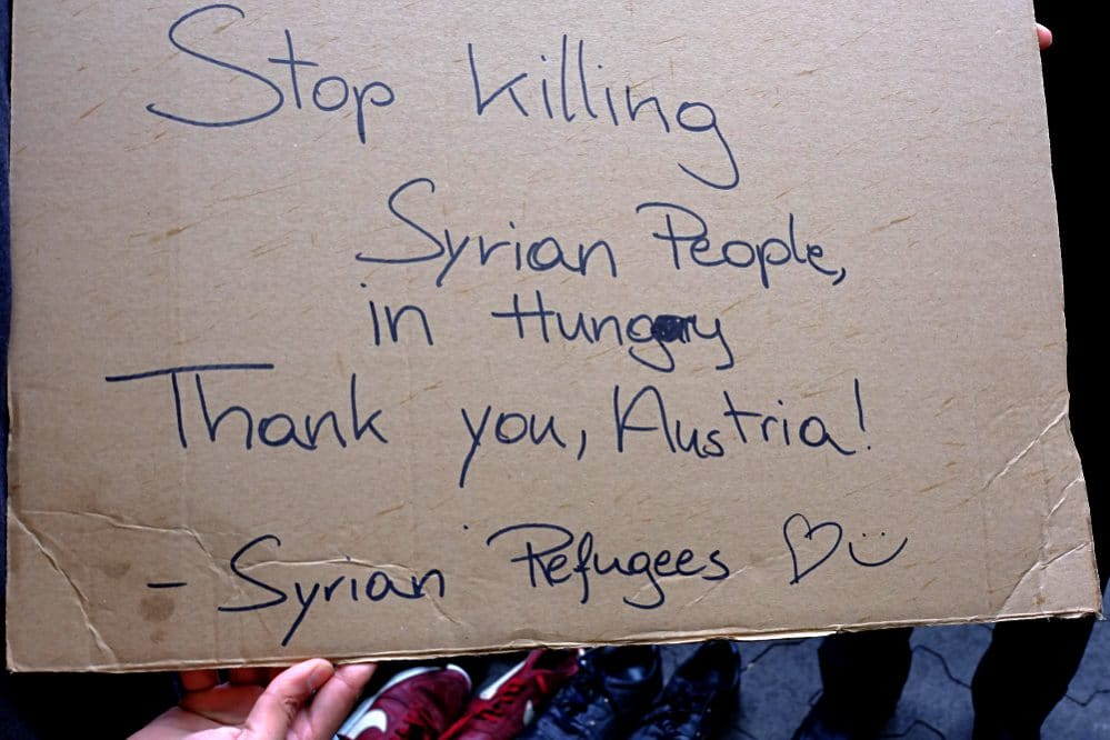 Syrian Refugees hold a sign: Stop killing Syrian Refugees in Hungary (today at Westbahnhof, Vienna)