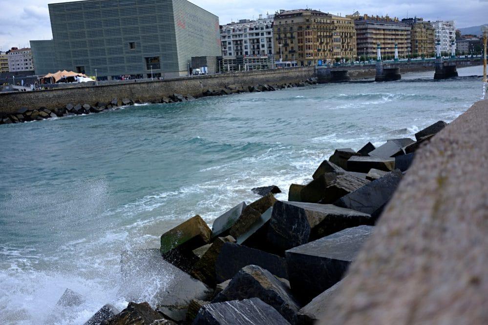 """Strömungsumkehr an der Mündung der Urumea in den Atlantik (baskisch """"ur"""" = Wasser, """"me(he)a"""" = schmal) . Im Hintergrund das Auditorio Kursaal in Donostia."""