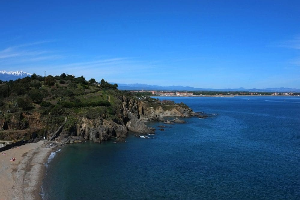 Im Hintergrund der Sandstrand von Argelès-sur-Mer und die Pyrenäen, die im Vordergrund, wie an der Costa Brava, ins Meer abtauchen.