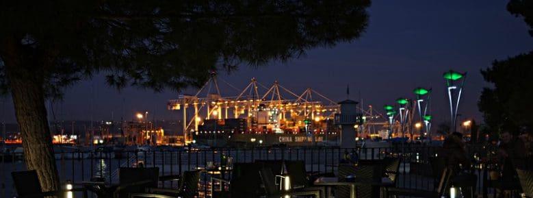 Der Hafen von Koper. Die Beleuchtung der Kräne erhellen die Nacht bis weit ins Hinterland. Die Geräuschkulisse kann bis ans Ende der Stadt wahrgenommen werden.