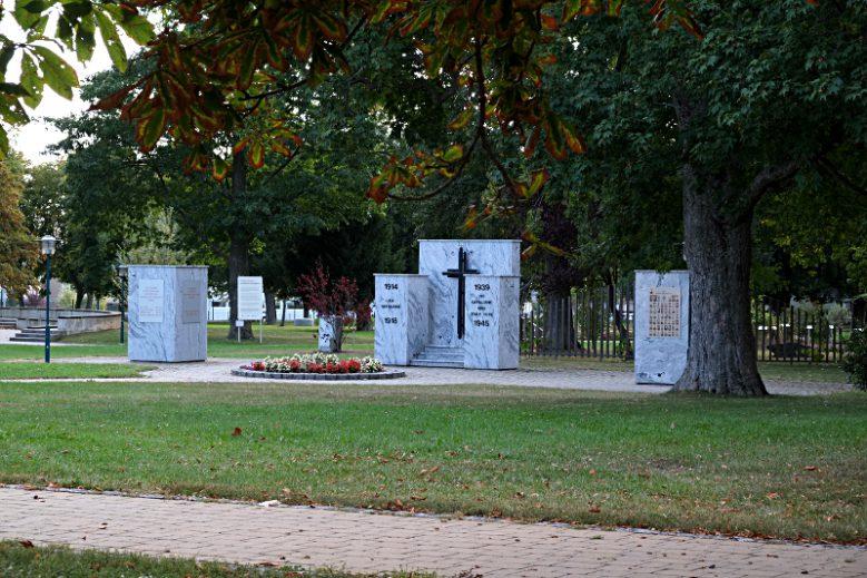 """Gedenksteine im Rechnitzer Schlossbergpark, auf der linken Seite befinden sich die Tafeln, die mit Inschriften an den antifaschistischen Kampf und an die Opfer des Nationalsozialismus erinnern. Auf der rechten Seite Tafeln mit Fotos """"Unserer Gefallener"""" in Nazi-Uniformen und ihre Namen."""