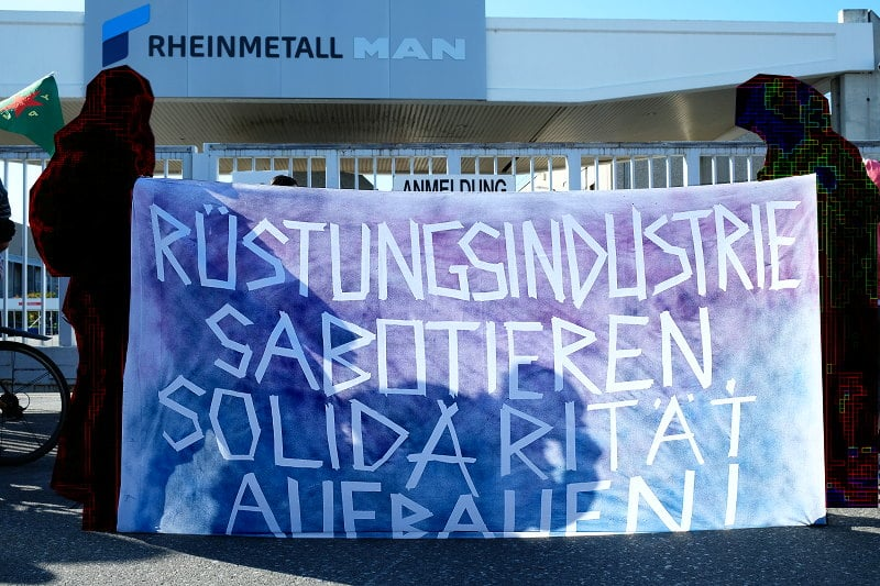 Mit den Menschen in Rojava solidarische Demonstrant_innen vor dem Rheinmetall Werk in Wien fordern auf einem Transparent: Rüstungsindustrie sabotieren, Solidarität aufbauen.
