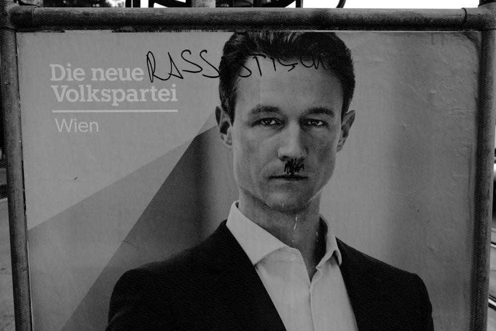 """Vandalisiertes Wahlkampfplakat mit der modifizierten Aussage: """"Die neue rassistische Volkspartei in Wien"""". Dem/der Spitzenkandidat_in wurde ein Oberlippenbart aufgemalt, der einschlägig zugeordnet werden kann."""